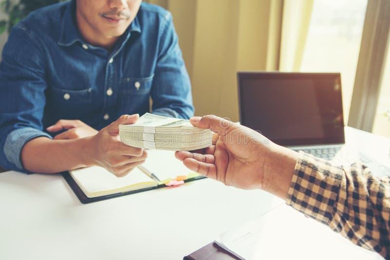 Uomo d'affari che dà soldi al suo partner mentre stipulando contratto - immagini stock libere da diritti