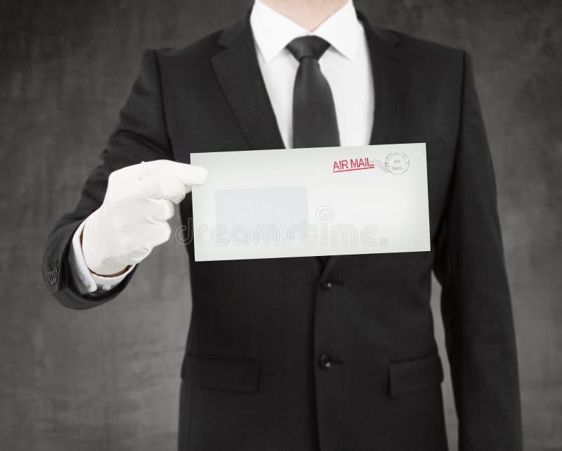 Uomo d'affari che dà una busta fotografie stock