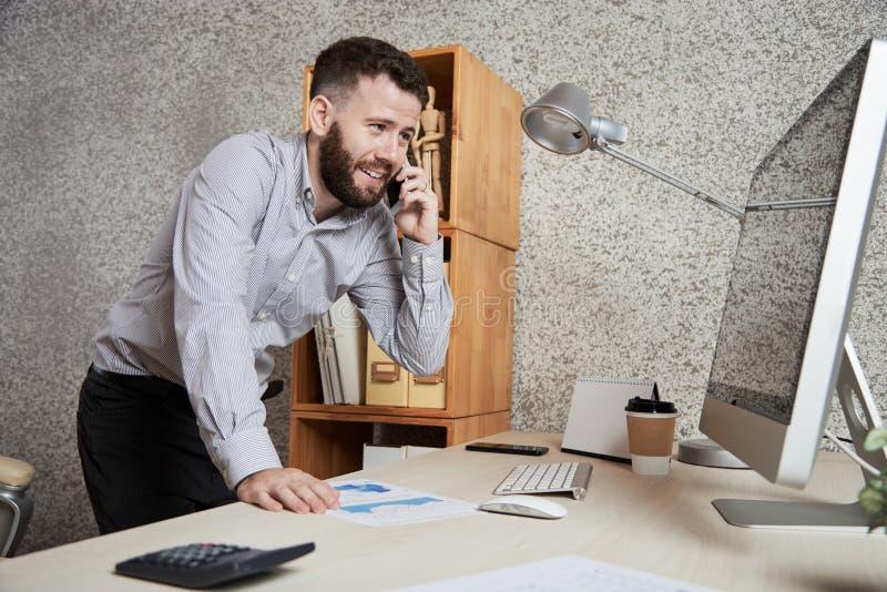 Uomo d'affari che discute lavoro sul telefono fotografie stock