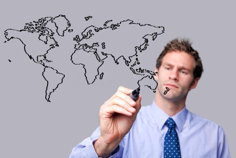 Uomo d'affari che disegna il mappa del mondo su uno scree di vetro fotografia stock