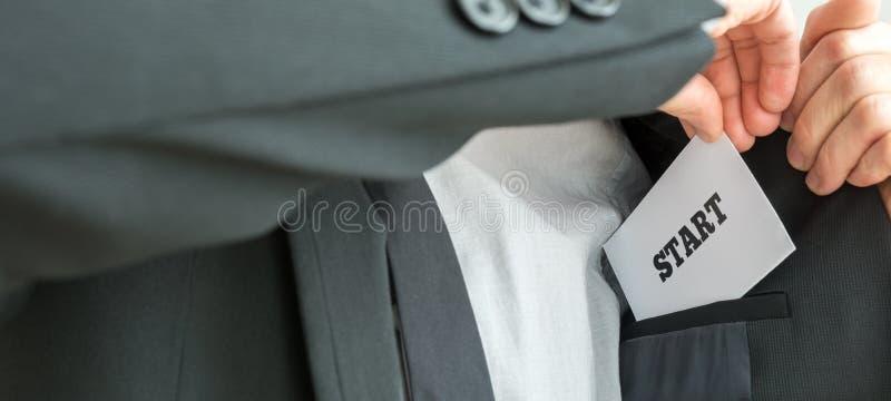 Uomo d'affari che dispone una carta bianca con l'inizio di parola immagini stock