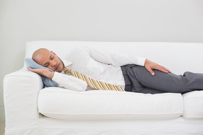 Uomo d'affari che dorme sul sofà a casa immagine stock
