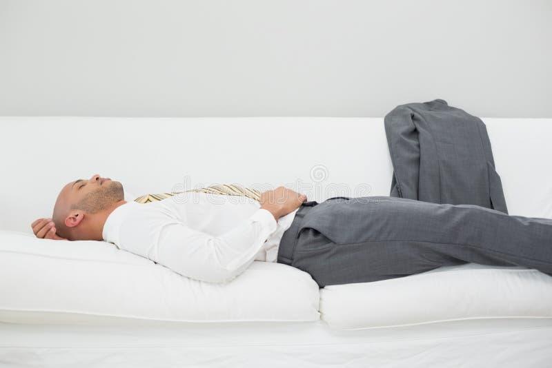 Uomo d'affari che dorme sul sofà a casa fotografia stock