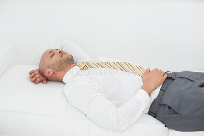 Uomo d'affari che dorme sul sofà a casa immagine stock libera da diritti