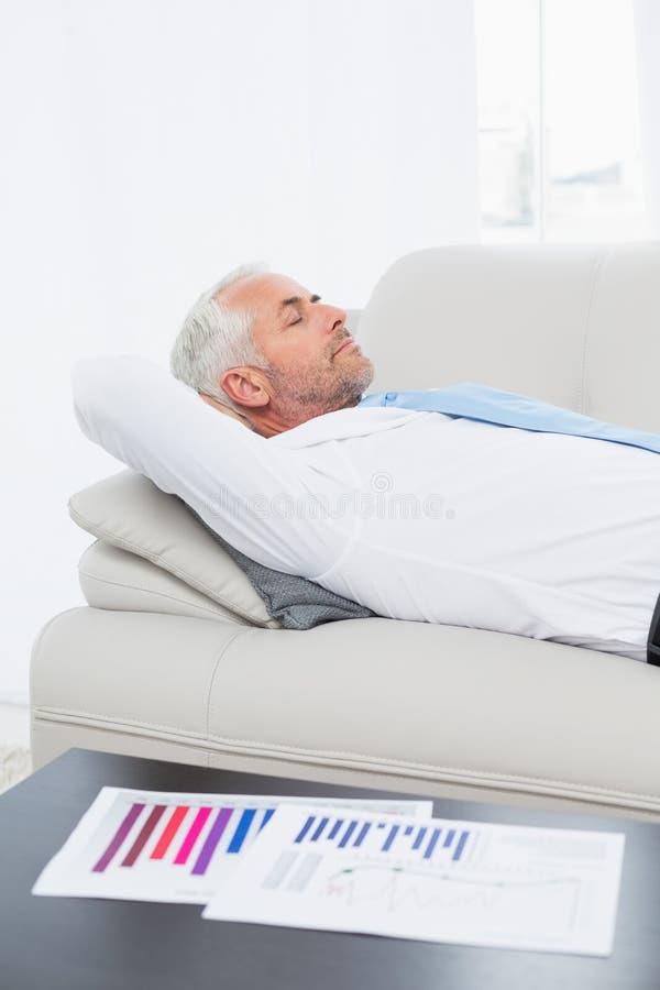 Uomo d'affari che dorme sul sofà con i grafici sulla tavola in salone immagine stock