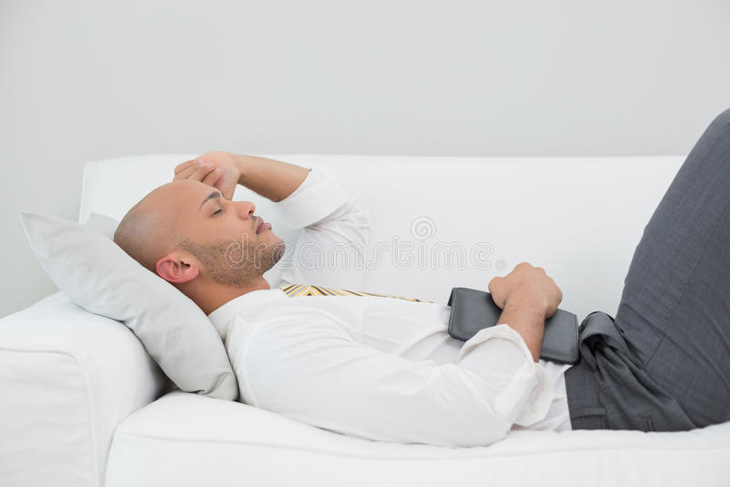 Uomo d'affari che dorme sul sofà con la compressa digitale a casa fotografia stock libera da diritti