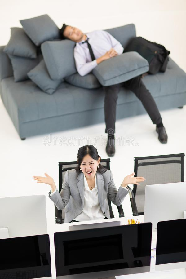 Uomo d'affari che dorme sul sofà nelle ore lavorative mentre wom di affari immagine stock