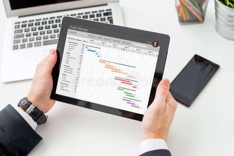 Uomo d'affari che esamina diagramma di Gantt sul computer della compressa fotografia stock libera da diritti