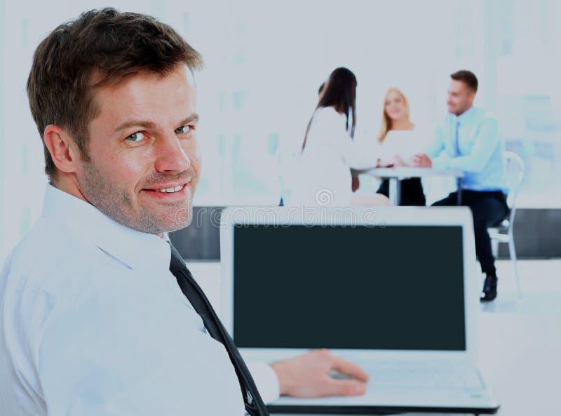 Uomo d'affari che esamina la macchina fotografica ed il lavoro sorridente il computer Ai precedenti il suo gruppo fotografia stock