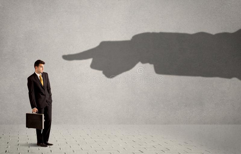 Uomo d'affari che esamina la mano enorme dell'ombra che indica lui concentrato immagini stock libere da diritti
