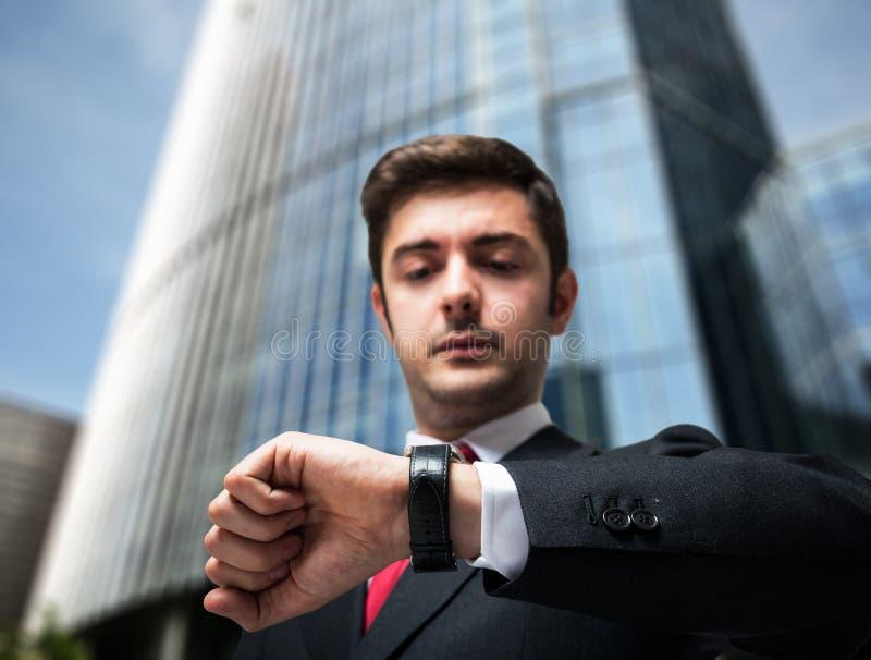 Uomo d'affari che esamina la sua vigilanza immagini stock libere da diritti