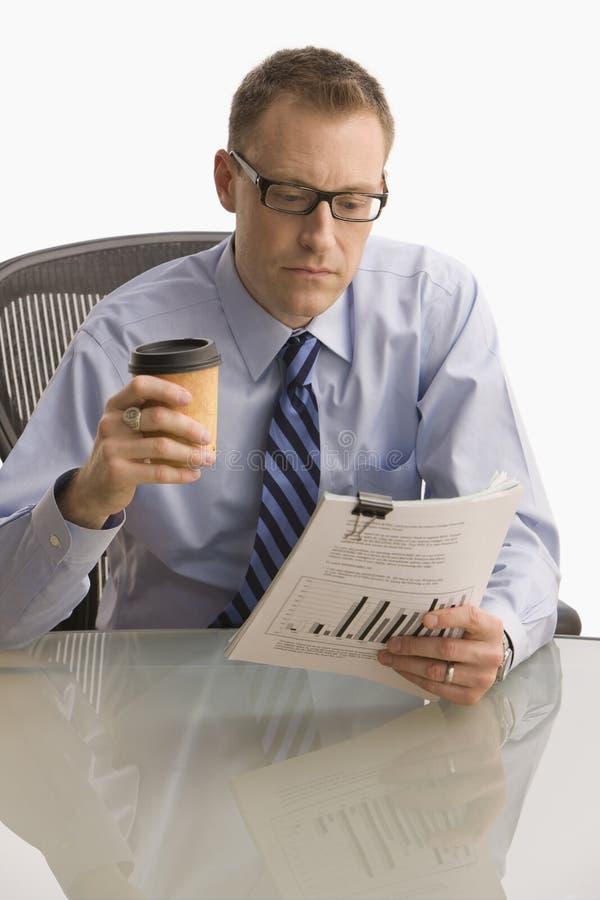 Uomo d'affari che esamina lavoro di ufficio - isolato fotografia stock libera da diritti