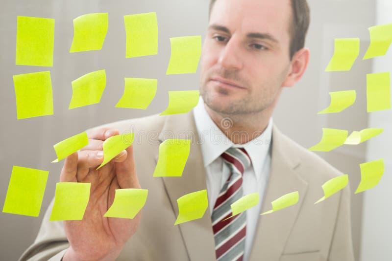 Download Uomo D'affari Che Esamina Le Note Adesive Immagine Stock - Immagine di appunto, bordo: 55353533