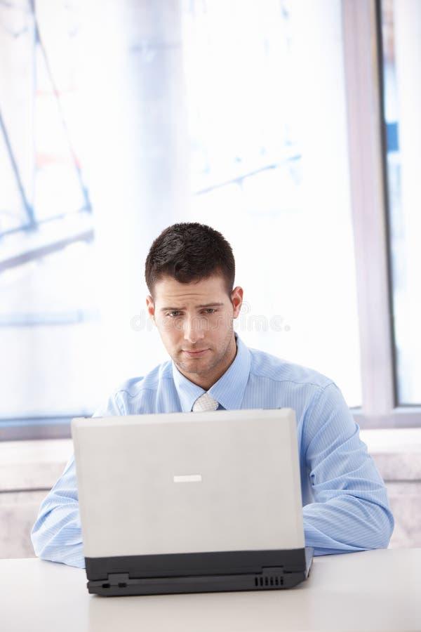 Uomo d'affari che esamina lo schermo del computer portatile disturbato fotografia stock libera da diritti