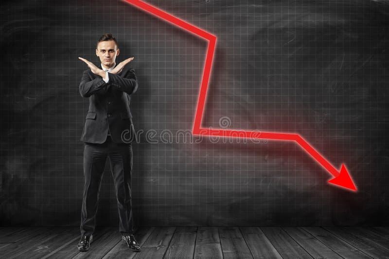 Uomo d'affari che fa gesto di rifiuto con la freccia rossa che va giù sul fondo nero fotografia stock
