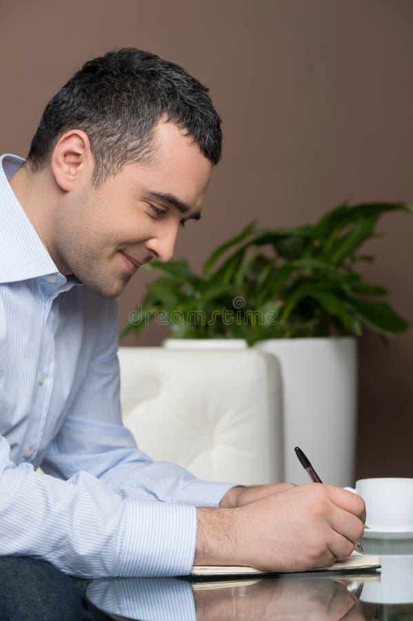 Uomo d'affari che fa le note fotografia stock libera da diritti