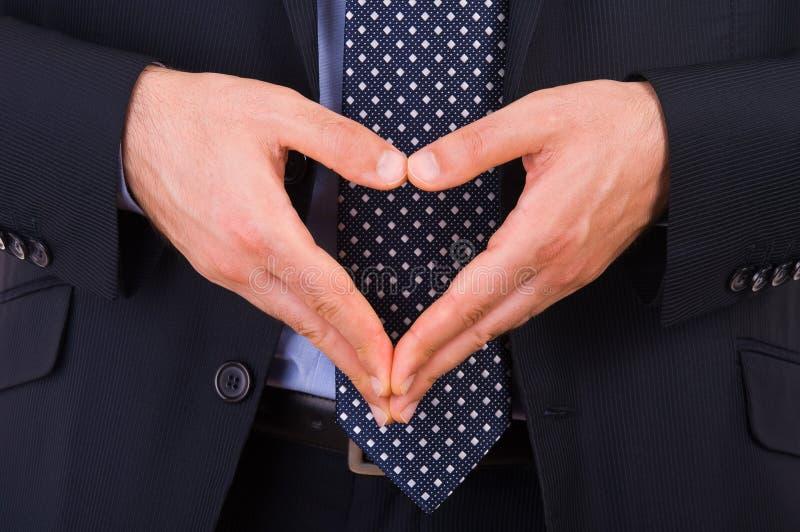 Uomo d'affari che fa simbolo del cuore con le mani. fotografia stock