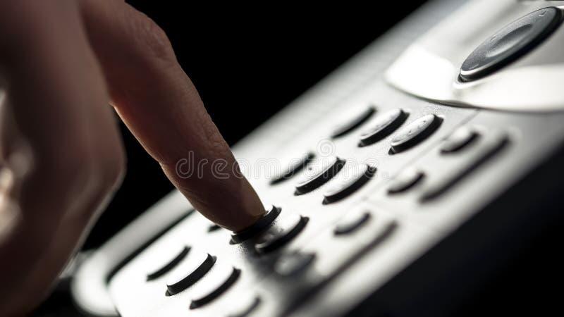 Uomo d'affari che fa una chiamata su un telefono della linea terrestre fotografia stock libera da diritti