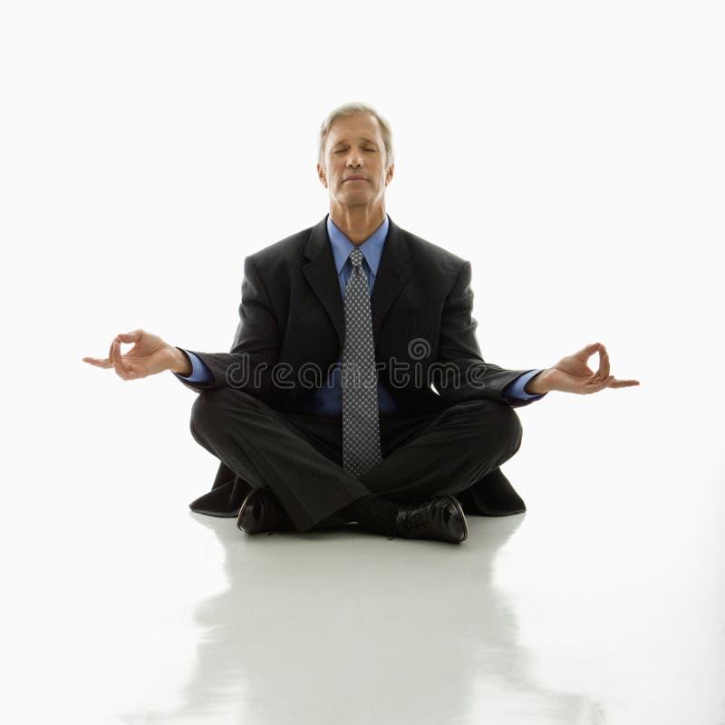 Uomo d'affari che fa yoga. fotografia stock