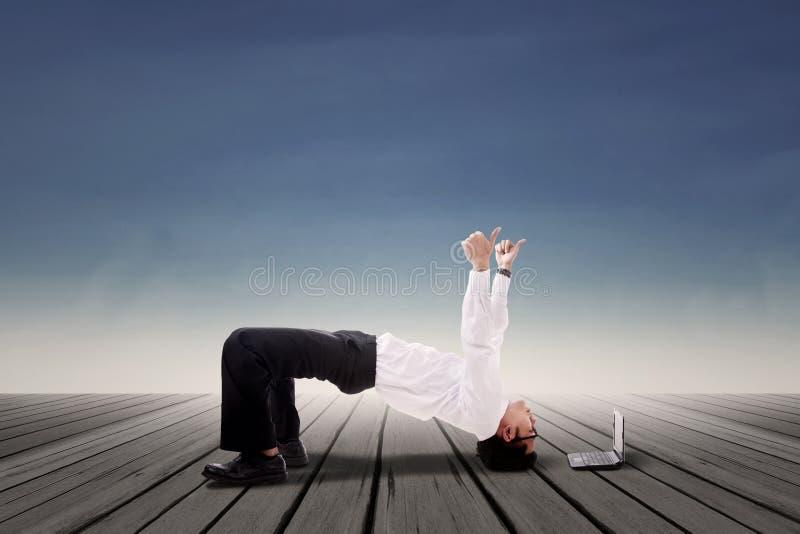 Uomo d'affari che fa yoga del ponte all'aperto fotografia stock