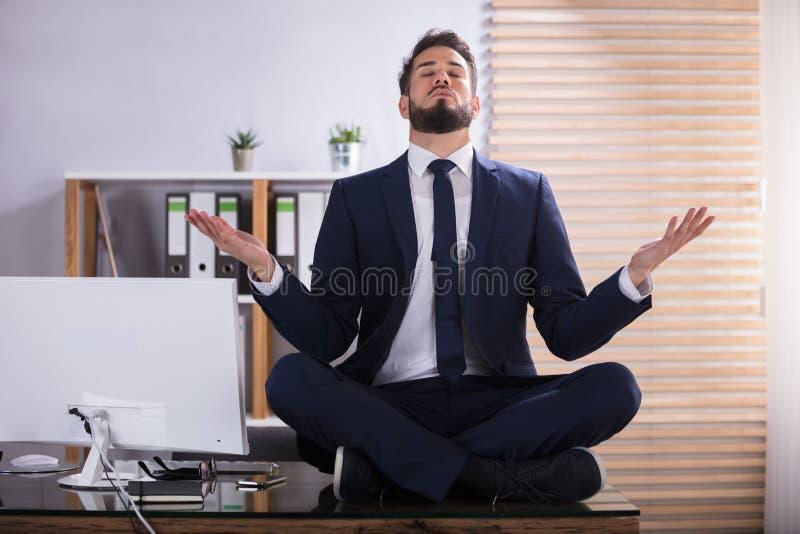 Uomo d'affari che fa yoga in ufficio immagini stock