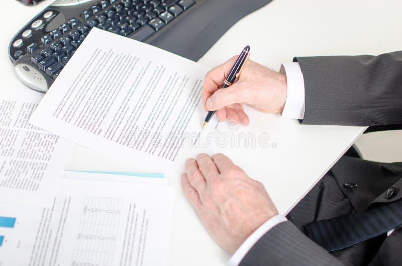 Uomo d'affari che firma un contratto fotografia stock