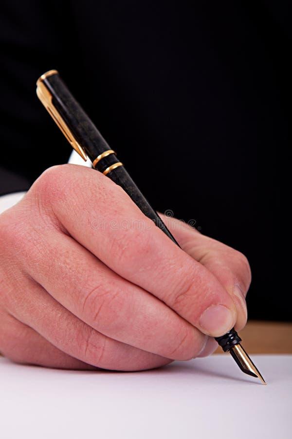 Uomo d'affari che firma un documento con la penna di fontana fotografie stock libere da diritti