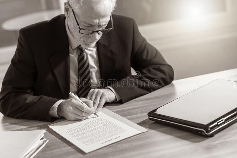 Uomo d'affari che firma un documento (il testo di lorem ipsum ha usato) immagine stock
