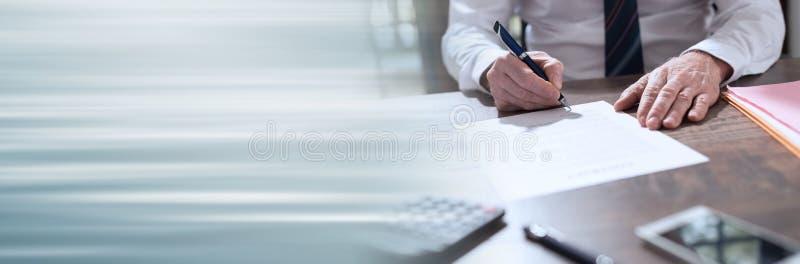 Uomo d'affari che firma un documento; insegna panoramica fotografie stock libere da diritti