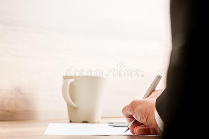 Uomo d'affari che firma un documento o un contratto fotografia stock