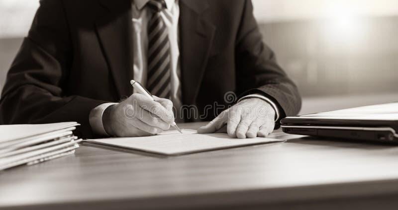 Uomo d'affari che firma un documento fotografia stock libera da diritti