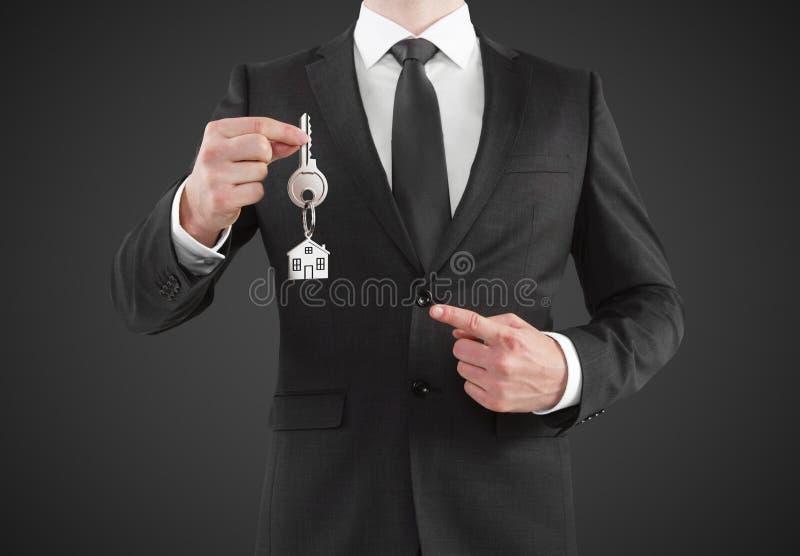 Uomo d'affari che fornisce una chiave immagine stock