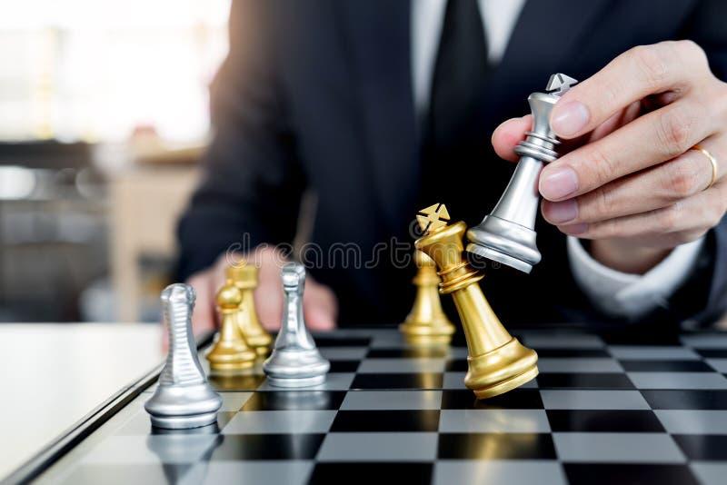 Uomo d'affari che gioca la figura di scacchi per prendere a per dare scacco matto un altro re con il gruppo, vittoria della gesti immagine stock libera da diritti