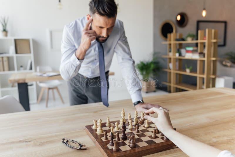 Uomo d'affari che gioca scacchi con il collega in ufficio fotografie stock