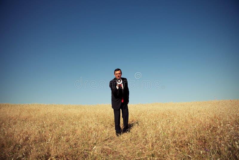Uomo d'affari che grida al megafono a voi fotografie stock