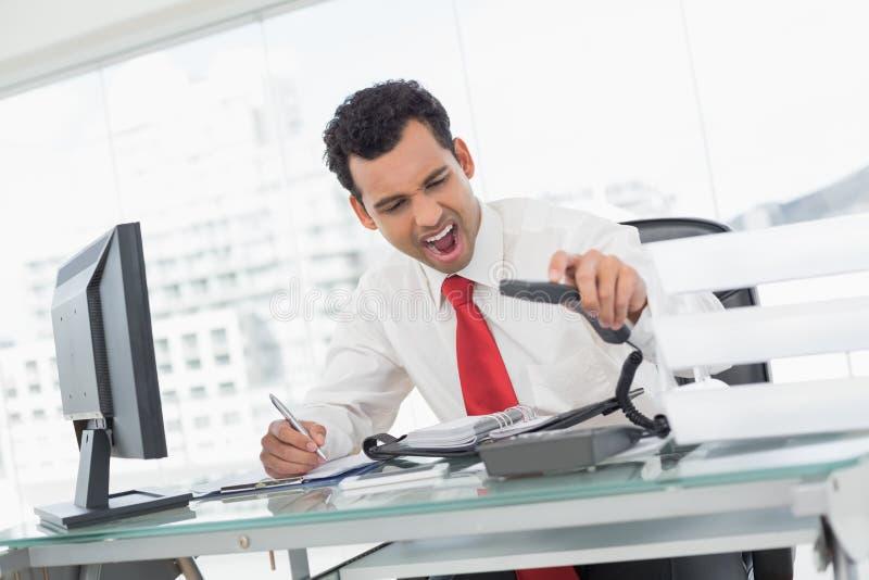Uomo d'affari che grida come tiene il telefono all'ufficio immagine stock libera da diritti