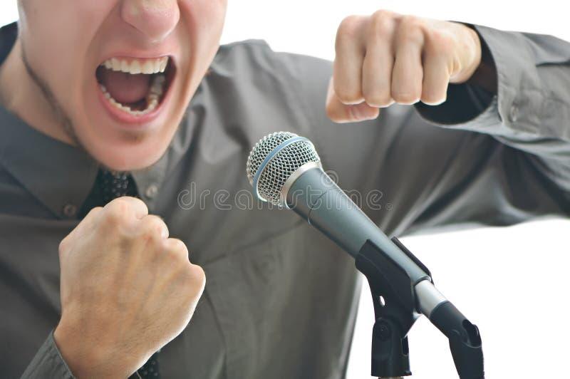 Uomo d'affari che grida in microfono fotografia stock libera da diritti