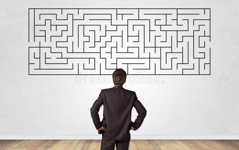 Uomo d'affari che guarda ad un labirinto su una parete fotografie stock