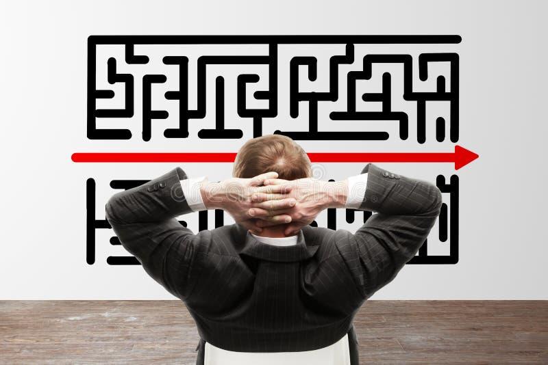 Uomo d'affari che guarda al labirinto immagini stock