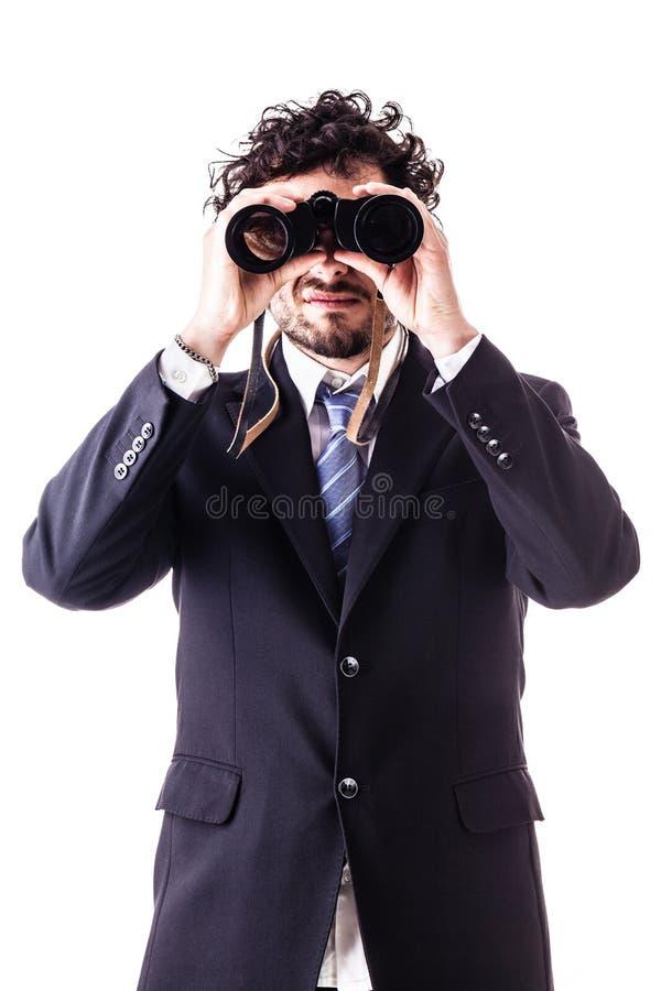 Uomo d'affari che guarda con il binocolo fotografia stock