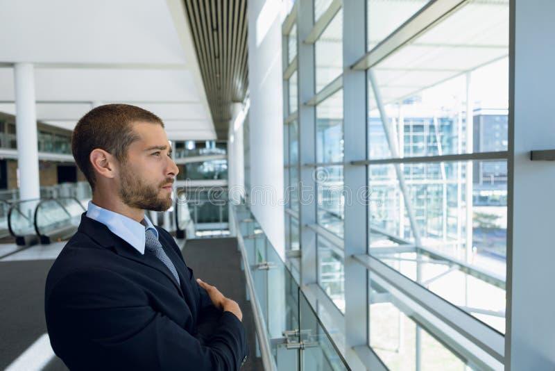 Uomo d'affari che guarda dalla finestra nell'ingresso dell'ufficio fotografia stock