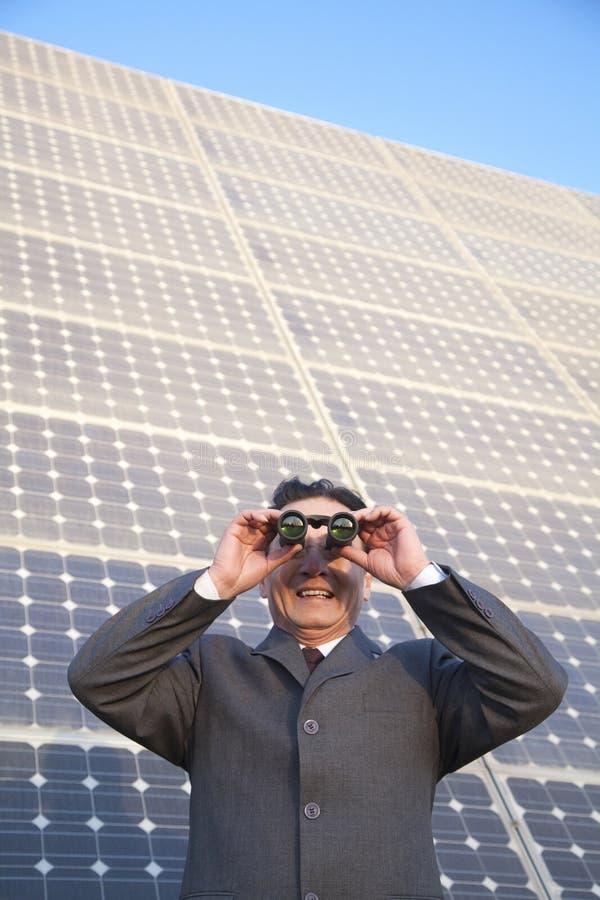 Uomo d'affari che guarda tramite il binocolo davanti ai pannelli solari immagine stock