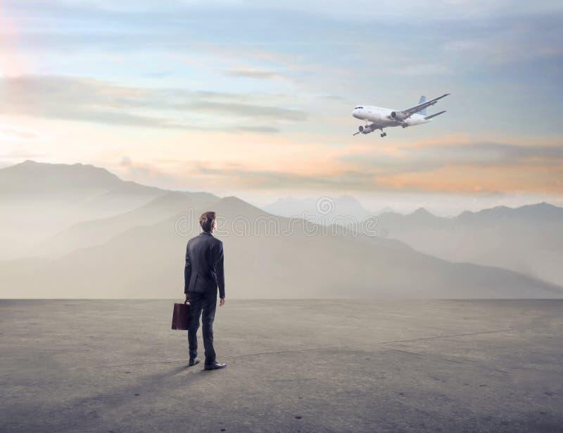 Uomo d'affari che guarda un aeroplano in un terreno incolto immagini stock libere da diritti