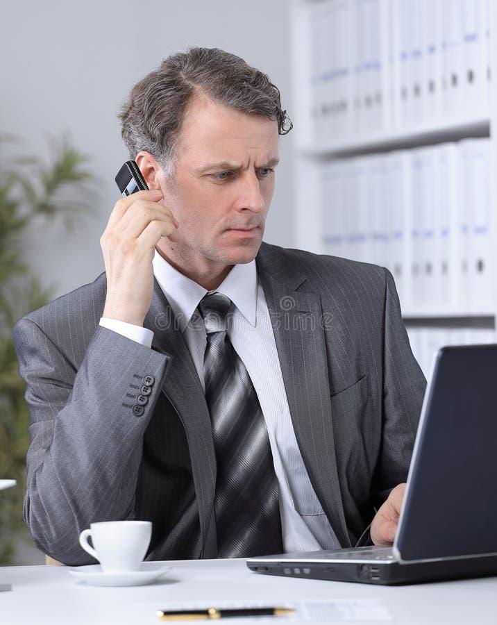 Uomo d'affari che ha conversazione di telefonata nel luogo di lavoro immagine stock libera da diritti
