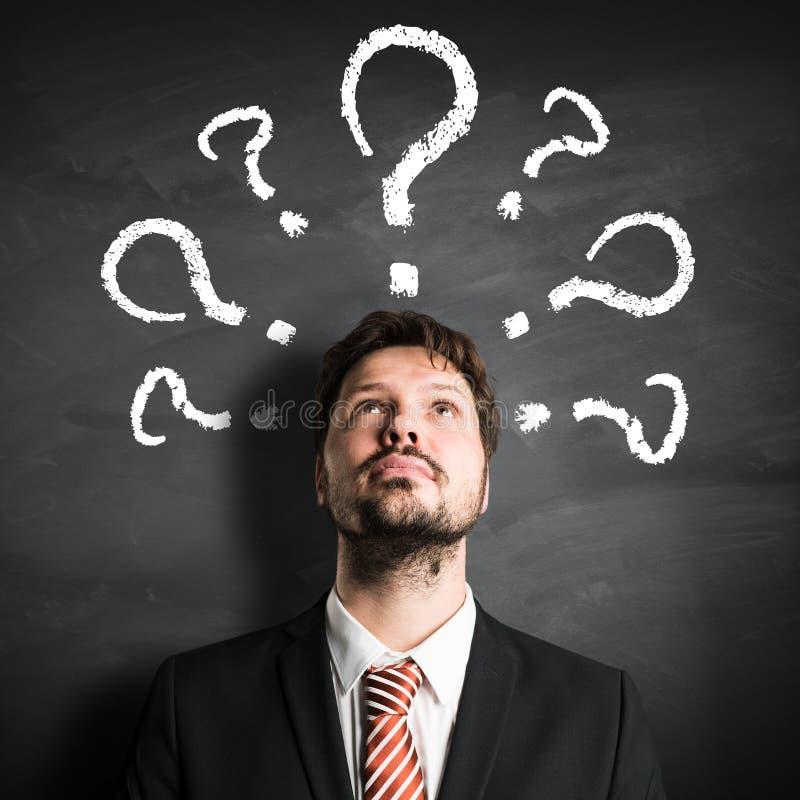 Uomo d'affari che ha molte domande simbolizzate come questionmarks su una lavagna fotografie stock libere da diritti