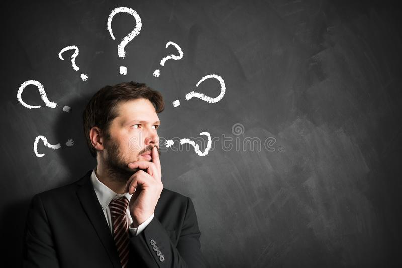 Uomo d'affari che ha molte domande simbolizzate come questionmarks su una lavagna immagine stock