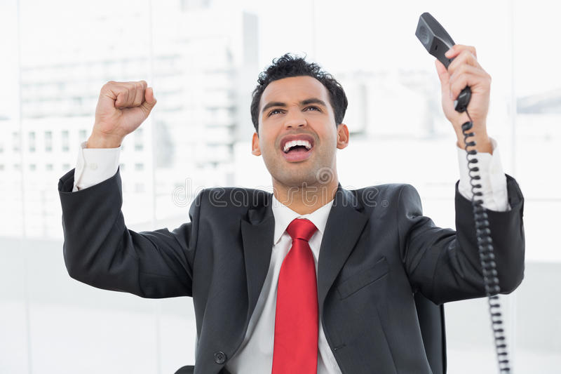 Uomo d'affari che incoraggia con il ricevitore telefonico all'ufficio fotografia stock libera da diritti