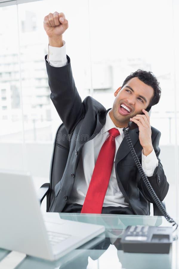 Uomo d'affari che incoraggia mentre sulla chiamata alla scrivania immagine stock
