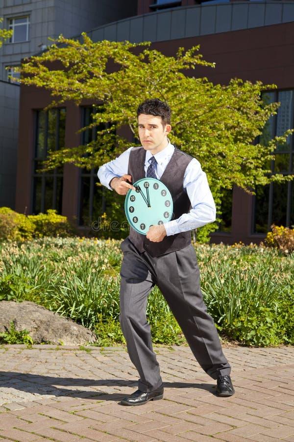 Uomo d'affari che indica all'orologio immagine stock libera da diritti