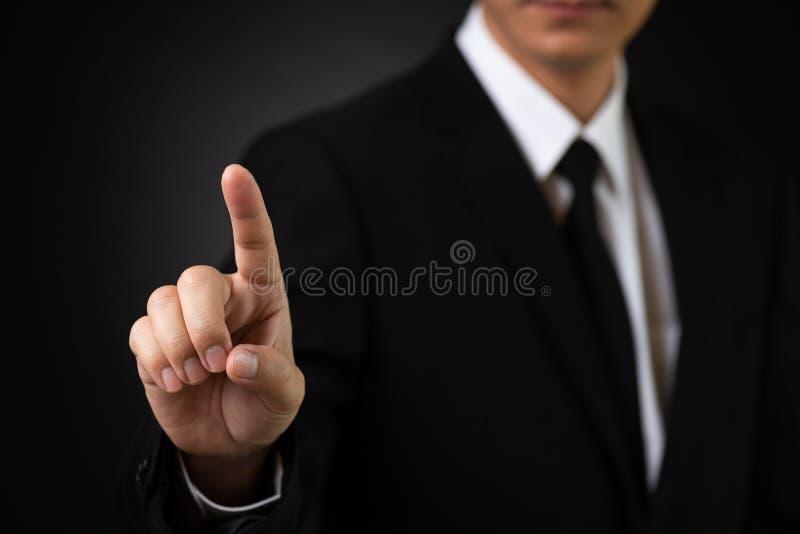 Uomo d'affari che indica con il suo dito contro il fondo nero Concetto di affari, di tecnologia e di Internet immagine stock libera da diritti